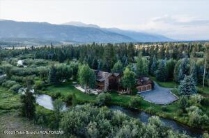 Located a few minutes from Wilson and approximately 20 minutes from Jackson Hole, this impeccable 5.88 acre estate encompasses Fish Creek and both sides of the East Fork of Fish Creek. A quintessential Wyoming property, bordered by 105 acres of protected lands, sits at the end of a private road and is nestled amongst a mature forest of quacking Aspens and stately Pine and Spruce trees. In addition to the extensive creeks on the property is an enviable trout-filled pond on the western portion of the property. ''A fly fisherman's paradise.''The hand crafted, custom log/timber and stone home, which was meticulously designed and built, exudes a timeless western feel and personality. With 7,000 square feet the home features five on-suite bedrooms with an