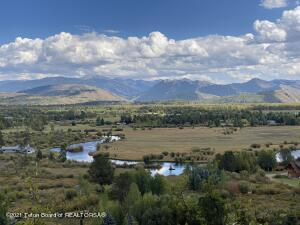 Rare find within walking distance to Wilson! Situated on a bluff 120 ft. above the valley floor with stunning 180-degree views stretch from the Tetons to Munger Mountain, this 7-acre parcel (two lots) is truly one of a kind! Overlooking the 381-acre Fish Creek Ranch, and several other conservation easements, the property is heavily wooded, full of wildlife, with no CC&Rs and lots of room to expand. The northern parcel is 3-acres with an older main house and a new 624 sq. ft. two car detached garage. There are plans for a guest house and the septic has already been upgraded to handle up to seven bedrooms and two kitchens on the north parcel. The southern parcel is 4-acres with a 2012 Carney designed modern 2-bedroom and 2-bath guest house. You can still built an 8,000 sq. ft. main house... ...and a 1,000 sq. ft. garage/shop/barn on the southern parcel Situated on a private dead-end road with all-natural landscaping, the views include the Grand Teton, Blacktail Butte, Sleeping Indian, Cache & Jackson Peaks, East and West Gros Ventre Buttes, Snow King Mountain, Pinnacle Peak and Munger Mountain. These parcels could make the perfect family compound.