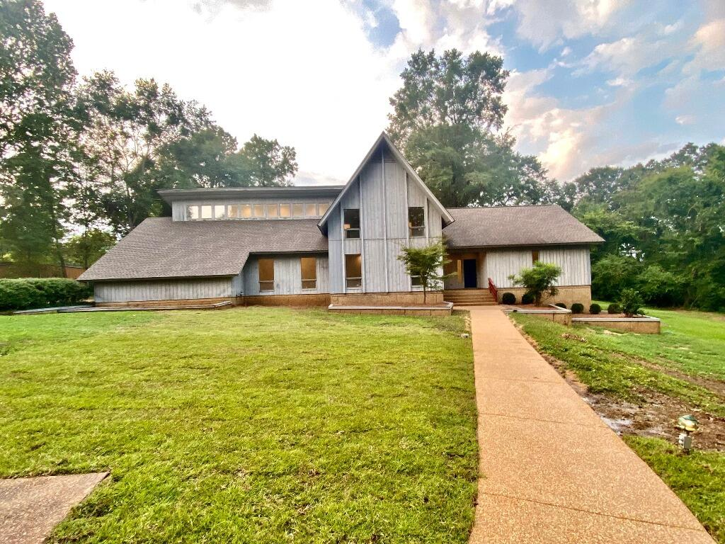 Rare Gem in the Heart of Tupelo! Beautiful contemporary home nestled on a park-like 5.15 AC lot. Home is 4BD/4.5BA w/lrg. kitchen & breakfast nook, lrg. formal living & dining, beautiful family room w/ hardwood floors, lrg. Fireplace & cathedral-style ceiling. The home radiates light with lrg. windows & on the main level, the master suite features lrg. walk-in closet, master bath & powder room. Upstairs features 3BD/2BA w/lrg. walk-in attics on both ends of house. Offers ample storage & a full basement w//12'' thick concrete walls & 8'' thick ceiling. Basement has lrg. room that could be finished as additional living space & a wine cellar, work shop & single car garage. Basement SF NOT included in Total SF on MLS listing. Taxes shown are estimated with homestead. All info subject to verif.