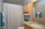 First story bathroom with a shower. Granite counter top, wood-look Porceline tile floor