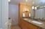 Granite counter top, custom built wood dual sink vanity with linen closet. Sconce vanity lighting, LED recessed can lighting