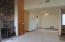 View of Formal Living Room with gas or wood burning fireplace. Vierw also shows formal dining area with access to 3 car garage & opens to kitchen area too!