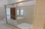 The master shower is partially enclosed with sliding mirrored doors, a built-in seat and opens on the far side for good ventilation.