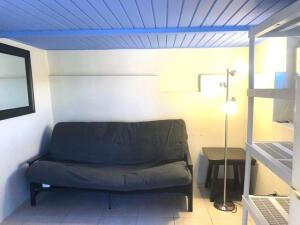 Studio furnished with a space saving futon that folds down into a bed, includes stove, fridge/freezer, water & window A/C unit.