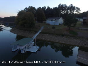 Affordable, well kept Smith Lake home for sale. 3 bedroom, 2 baths. Open floor plan. Approximately 130ft of year round water. Single slip boat house with swim pier and 6000# boat lift. Large detached 24x36 garage with 2 additional carports. Plenty of room to store those water toys.