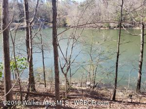 Perfect for RV, camper or mobile home. Waterfront lot on Rock Creek with approx. 140 ft of year round waterfront. Very mild slope with easy access to the water. Very few lots on Smith Lake as nice that allow campers and mobile homes. Must see this one.  Don't wait!!