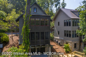 EASY LIVING ON SMITH LAKE IN THE EXCLUSIVE GATED COMMUNITY SILVEROCK COVE!  This waterfront cottage offers an open floor plan with shiplap walls  & wide plank flooring.  Kitchen w/ granite c'tops & stainless steel appliances overlooks the dining & family rm & offers wonderful lake views. Upstairs is a spacious master suite w/ 2 closets  + en-suite guest room. The walk out basement features another family rm with wet bar,  bedroom #3 & a full bath. Enjoy coffee from the main level screened porch or the lower covered patio. Deck is temporary.Please call for details.A lighted boardwalk surrounds the community. 2 salt water pools, clubhouse, & dry boat storage w/ boat concierge! Year round water