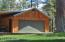 Car port and tack room are attached to garage. Separate hay and feed shed nearby.