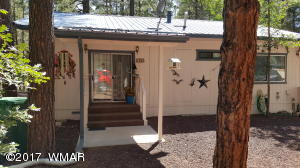 Front view with sliding glass door & covered deck. Newer metal roof. Sweet little home!