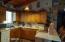 Roomy kitchen w/plant shelves, gas stove, dishwasher, refrigerator.