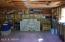 Painted floor, shelving & window in roomy garage.