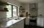 Kitchen sink, picture window, gas range and stainless steel hood