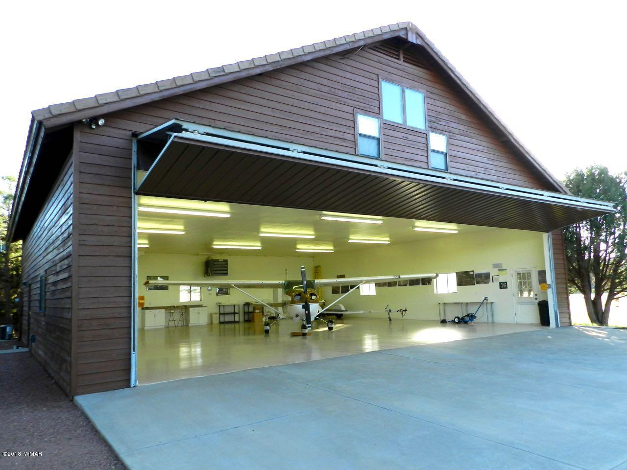 Watch all of the action from your Mid-Field 50' x 50' Hangar with a furnished 700 sq-ft apartment above located on a 0.95-acre home lot at the prestigious Mogollon Airpark (AZ82).  The apartment features an eat-in kitchen with granite counter tops, gas oven/range, dishwasher, microwave and refrigerator. The adjoining family room is furnished in a casual and comfortable style.  Skylights and solar tubes provide daylight lighting throughout.  The bathroom features a beautifully tiled shower and tiled vanity with double sinks.  A spacious 14' x 14' furnished master bedroom completes the interior space.  Stacked washer/dryer hookups.  A tankless gas water heater and re-circulating pump provide instantaneous unlimited hot water. Winterization bibs allow for complete water draining.