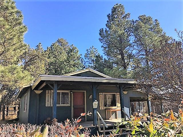 Adorable, Cozy Cabin in the Pines!! Open floor plan, 1 bedroom, 1 bath with an additional multipurpose room for an Office, Den or Visitors! It has a Carport and a Covered Front Porch to Enjoy the Long Cool Summers in the Forest! Must See!!