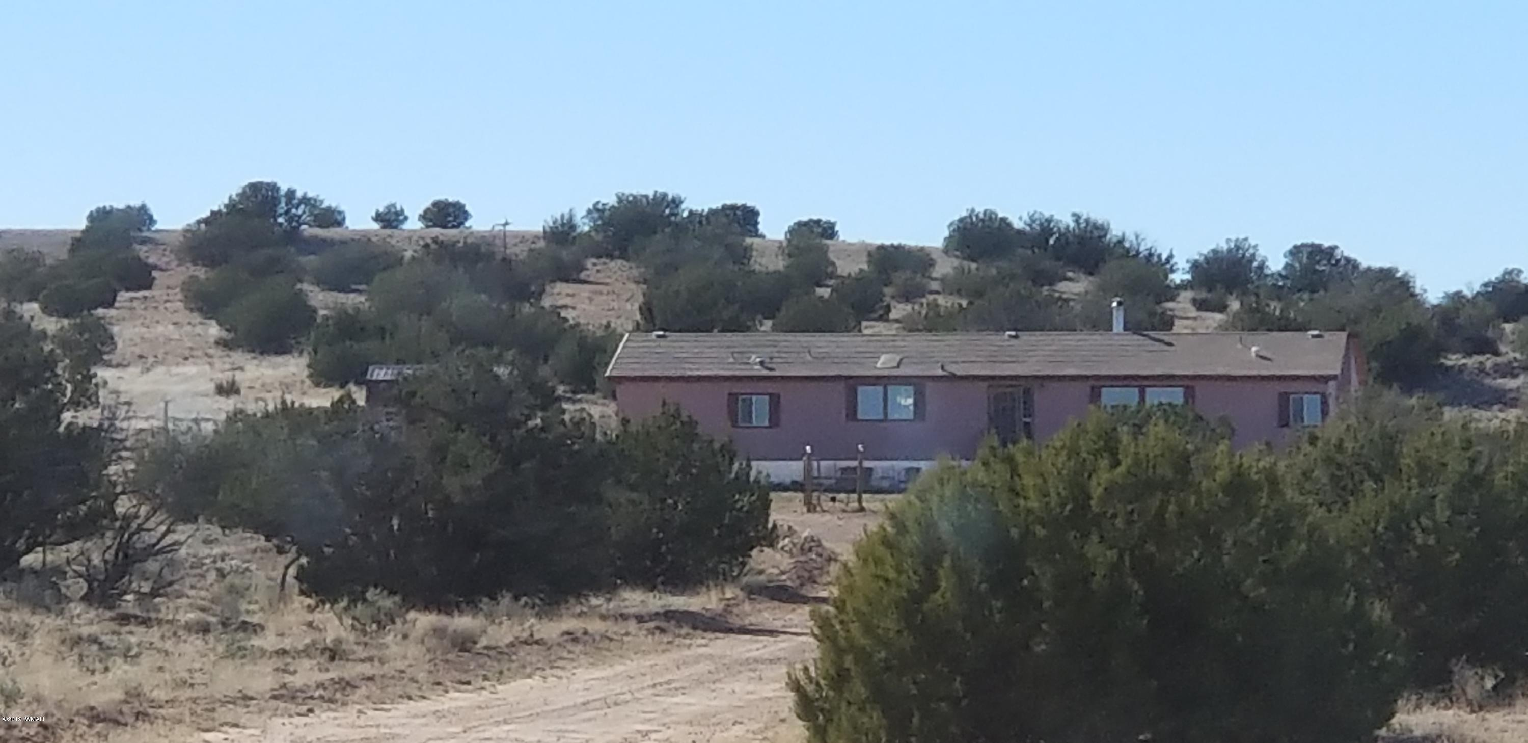 Off the grid homestead, this house is a must see! All solar & water systems are running. Privacy w/amazing views. Full 37-ac with desert wildlife & exploration. Sits on a corner tract w/over 1/2 mile of road frontage. 3+ acres are fenced, also fenced livestock areas with a 4 stall goat/sheep pallet barn & a fenced/netted chicken run w/converted camper coop. The laying flock & milking goats are available for purchase. The home has 3BR & 2BA w/bonus room. 2010sf w/26 exterior walls & well insulated drywall inside & texture throughout. Remodeled in 2016 w/Pergo laminate flooring, new carpet in BR's, Granite countertops w/hammered copper farmhouse kitchen sink, double inlaid copper sinks in guest BA, basin sinks w/fountain faucets in MBA, slate & travertine hearth area w/wood burning stove,
