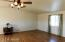 Large, open living room features the warm glow of wood laminate flooring, vaulted ceiling and ceiling fan.