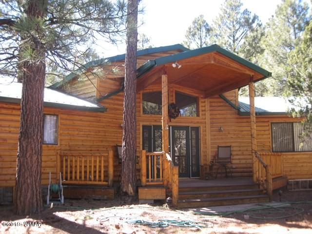 Awesome log sided single level cabin offers rustic richness throughout with knotty pine T & G walls and vaulted ceilings, and wood flooring in great room and living room.   Spacious great room has a gas fireplace in addition to pellet stove and central heating,  and a wet bar for entertaining. Open floor plan to living room, kitchen and dining area.  Many furnishings are negotiable.  Enjoy the towering ponderosas from the two covered decks and the privacy offered on the corner parcel that is over 1/2 acre.  Newly added detached 2 car insulated garage has place to plug in your RV.