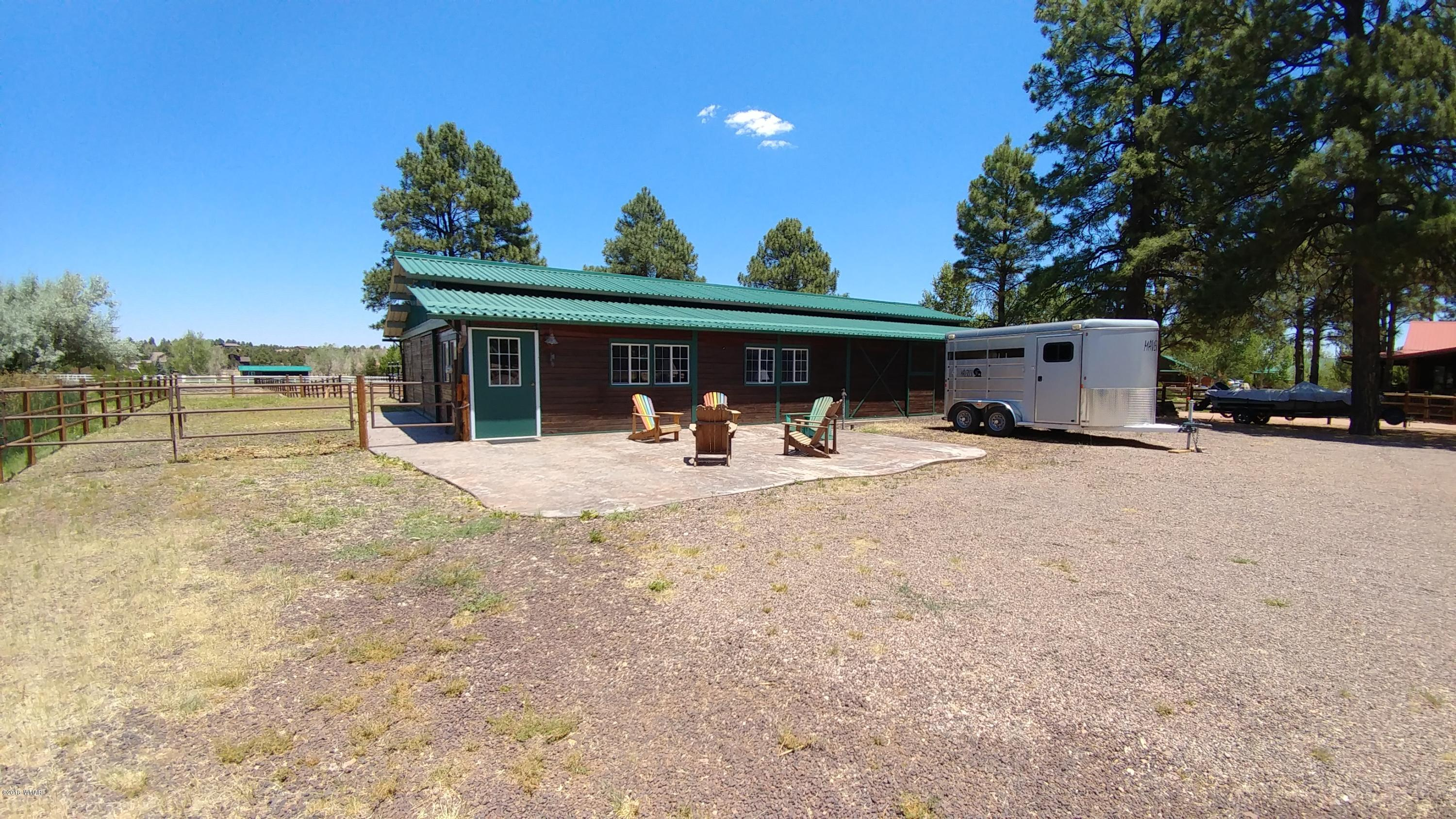 Horse Lovers! Build your dream cabin on this 1.53 acre lot with a beautiful Castlebrook barn already built. The 2560 sq. ft. barn has 6 stalls, tack room, feed room and a 11.6 X 32' separate area with living room/sleeping area, a small kitchen area that includes cupboards, microwave, small refrigerator and a separate room for toilet and sink all heated by base board electric heaters. Stalls have Nelson heated waters and feed bins, 4 stalls have turn out pens. Seller recently put in a 96'X64' fenced in arena. All this on a private pond and fenced in pasture area. The property has several tall pine and level open area to build a cabin. Ride out to the National Forest right from your property.. This is a rare find in the White Mountains! Come and enjoy all the seasons in this beautiful area