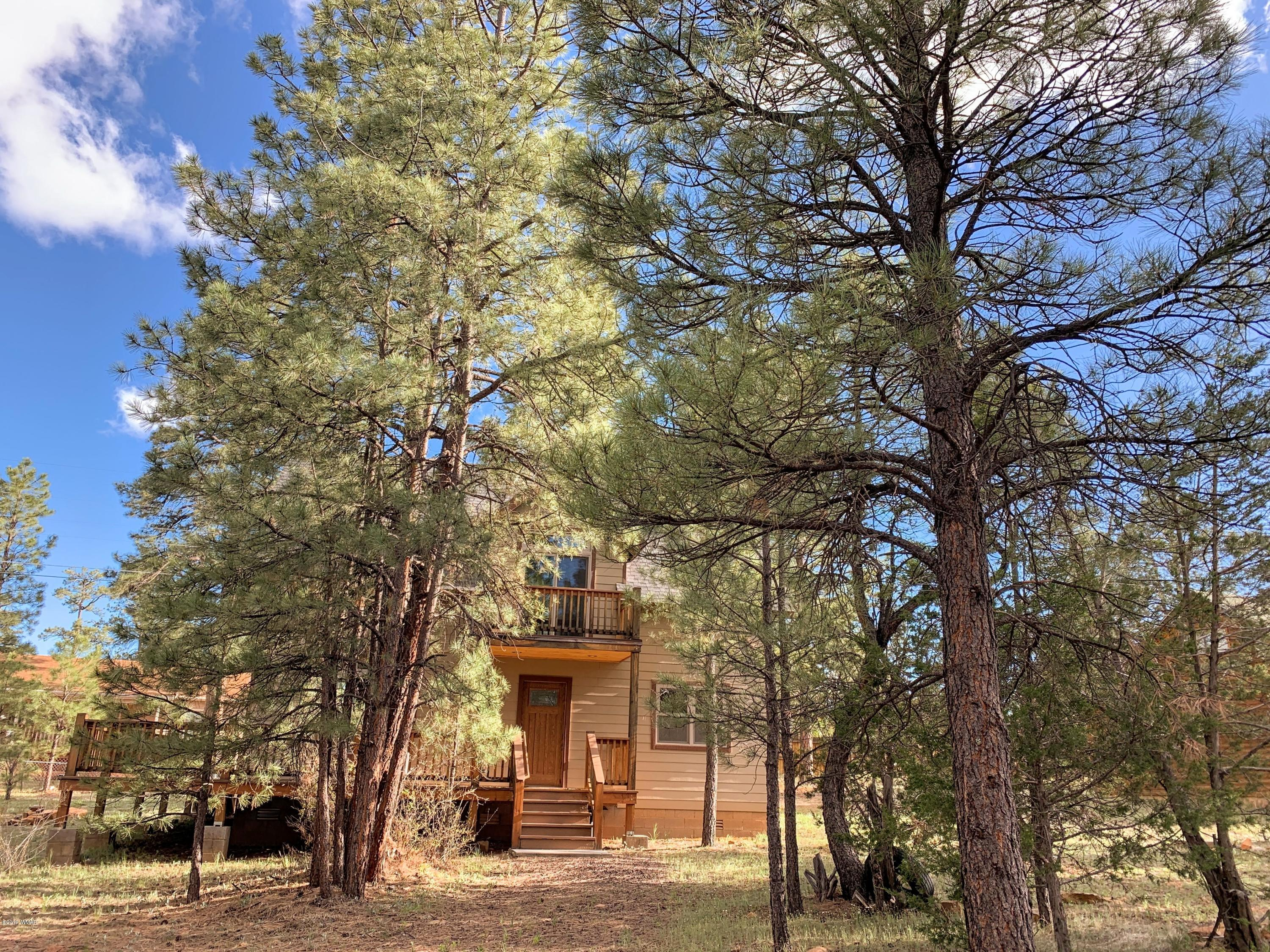 Behind the trees and encompassed in the towering ponderosa pines you will find your mountain getaway. The 2 story wood vaulted ceiling provides a spacious retreat. The wall of windows brings the outdoors in. Open floor plan with cozy kitchen and granite counter tops and breakfast bar is perfect for entertaining.  There is 3 bedrooms and 2 full baths. The master has a large walk in closet and unique wood vaulted ceiling with a  deck to enjoy the view of the ponderosa pines. Plenty of storage and a utility room. Private feel with the large yard. Move right in and enjoy the white mountains.