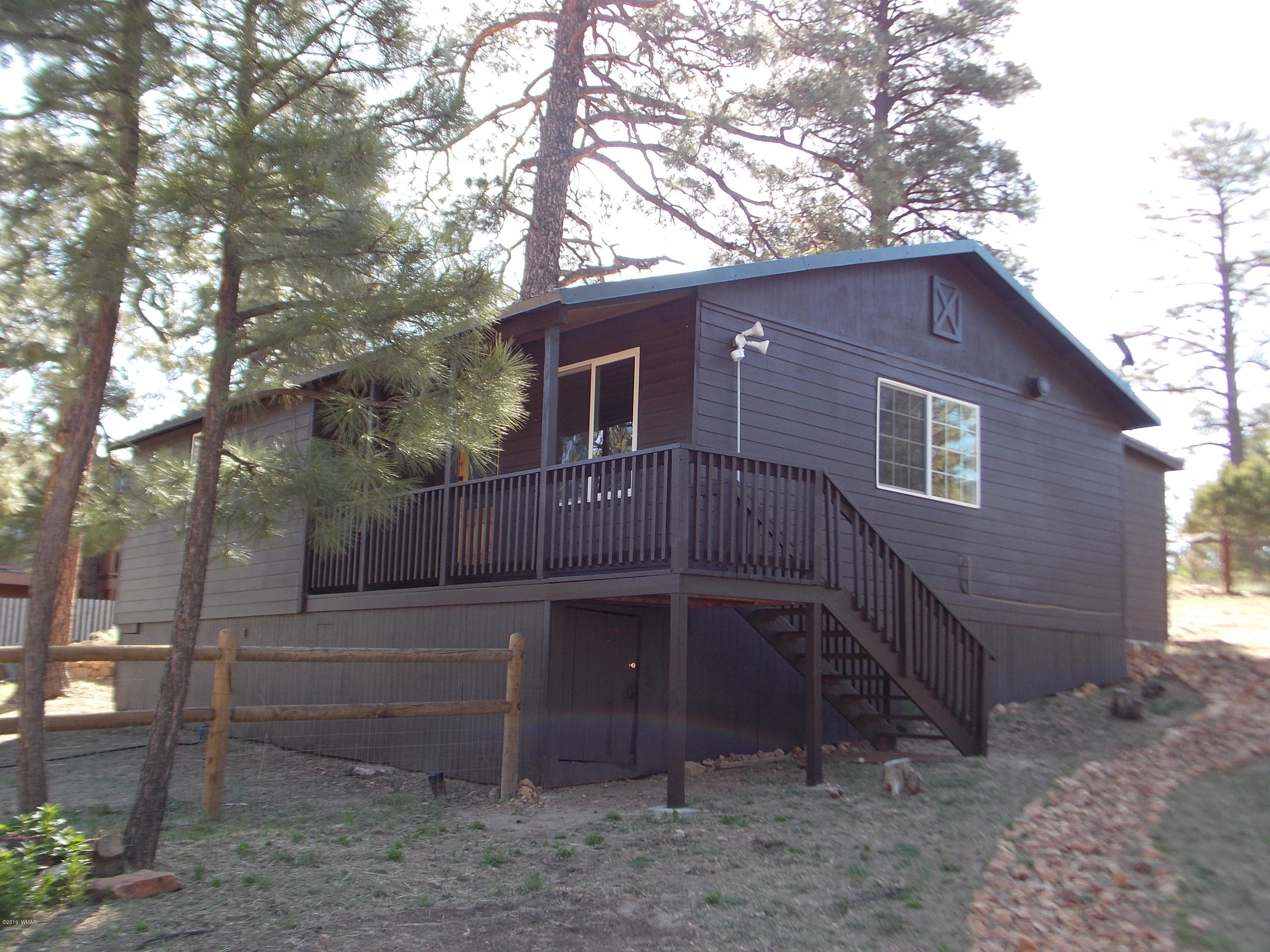 Great cabin for  the kids and Fido to have plenty of fun in the fenced yard with kids play area.  Enjoy all year long for a full time residence or use as that summer get-a-way to get out of the heat.  Freshly painted exterior-METAL roof-new deck off the master BDRM-skylights-vaulted T&G ceiling -and laminate flooring throughout.  Screened in porch-large-shed for plenty of storage-RV gate and plenty of parking.  One of the larger lots in the neighborhood as it is .45 of an acre.