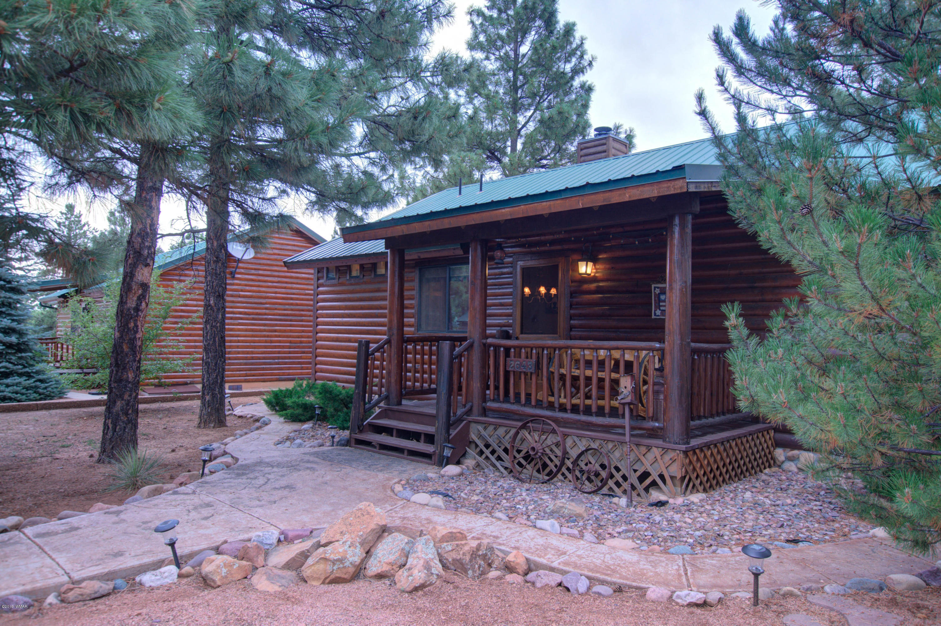 Cabin in the pines! This fully furnished 2 bedroom, 2 bath popular split floor plan Bison Ranch cabin is nestled amongst tall pines.  Charming interior with cozy decorator touches as well as a nicely landscaped yard- stamped concrete walkways and gathering area off the full length rear deck.  Well maintained and never used as a rental.  Bison Ranch amenities include sports courts, kiddie playground, catch and release fishing pond, as well as shopping and dining.
