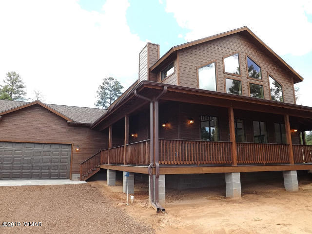 Gorgeous 2300 SqFt, 3 BR/2.5 BA New/Under Construction home situated on a very nice heavily treed 2.12 acre homesite in Overgaard!. This home will feature a great room design, porcelain tile, engineered laminate flooring, carpet, granite countertops, travertine tile in the showers/baths, T&G knotty pine ceilings, knotty hickory cabinets, knotty pine interior doors, stone faced  fireplace, large laundry/mudroom with cabinets and granite counter top, central heat/AC, a generous loft, interior log rails, a 10' lodgepole and exposed wood beams. The exterior will feature smart side low maintenance siding, a 3/4 wrap around covered deck with composite decking and an oversize attached two car garage. The master suite is downstairs and offers a separate private entry/exit. The Photo is a duplicate