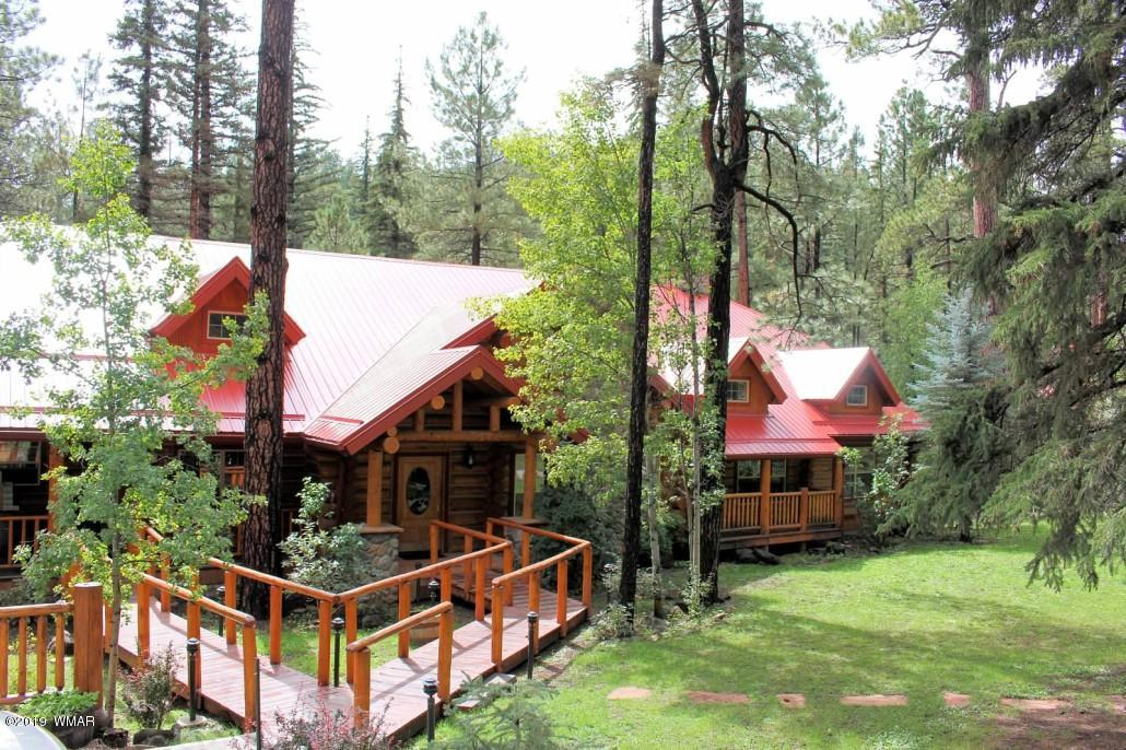 Currently utilized as a premier venue, a lodge perfect for reunions or retreats and 4 cabins available for nightly rentals. The property sits on 4+ acres and could easily be used as a family compound! There are 4 parcels: 2 parcels are on the West side of the River and include the 9 bedroom, 9.5 bath lodge, the 2 bedroom, 2 bath cabin, an outdoor bathroom with 2 baths (one is handicap friendly) and an acre lot to potentially build an additional cabin.  The other 2 parcels are on the East side of the River & include a large 5 bedroom, 3.5 bath cabin with 2 master suites & two 1 bedroom + Loft cabins and a separate building for additional laundry and pump for the wells. Septics and wells service all log cabins, there are great wood carvings on site, 2 bridges, 3 fire-pits & 2 horseshoe pits