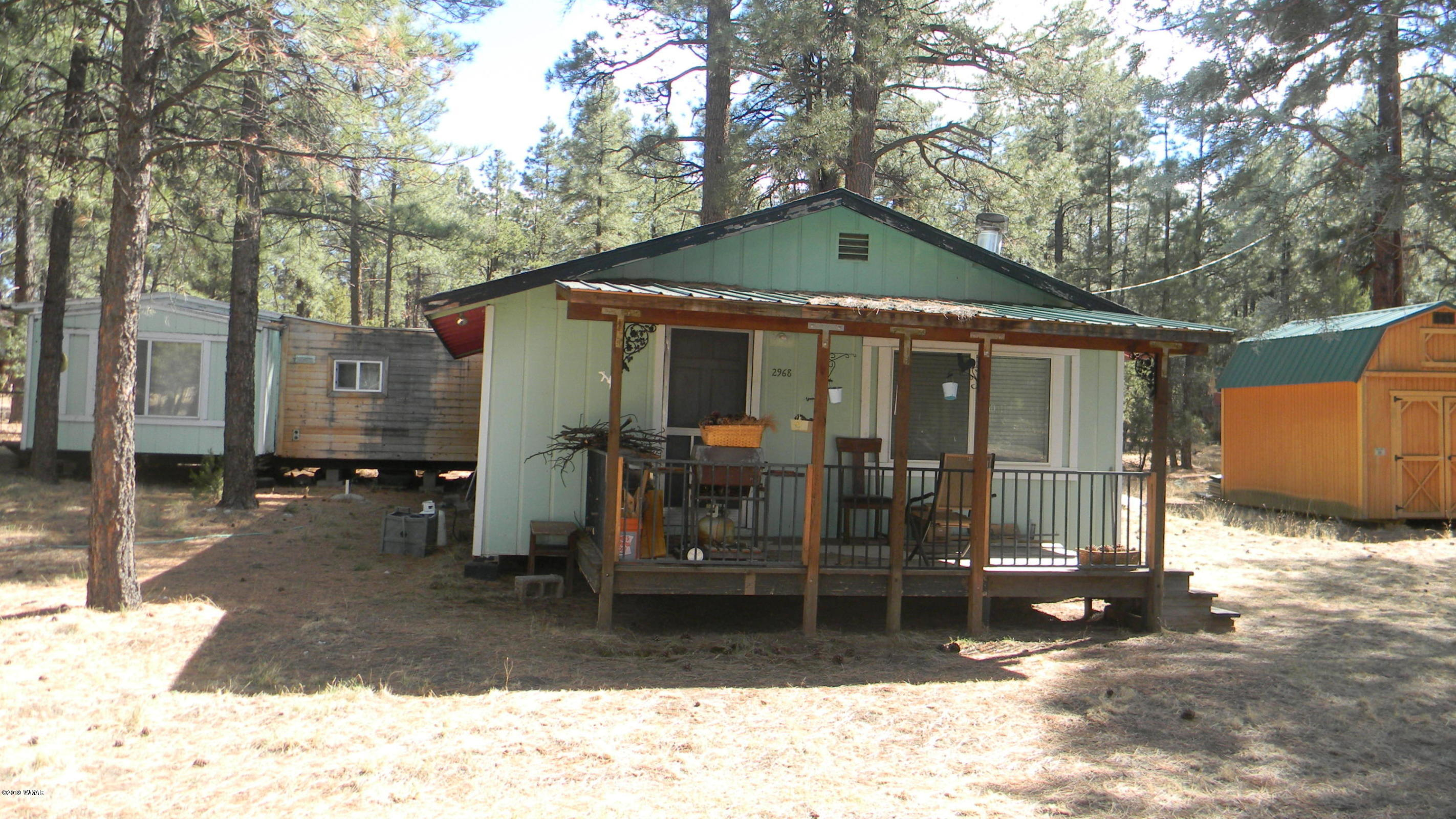 FANTASTIC RENTAL OPPORTUNITY!  Our just extra space for friends and family. Mobile with add on located on .23 acre lot. Unique layout offers 2 separate living quarters. Has lots of tall pines, in a quiet neighborhood with very little traffic. On a paved, county-maintained road, just minutes away from stores, restaurants, and national forest. Recently re-plumbed throughout with Pex. Owners' opinion of square footage differs from county records, buyer to verify.