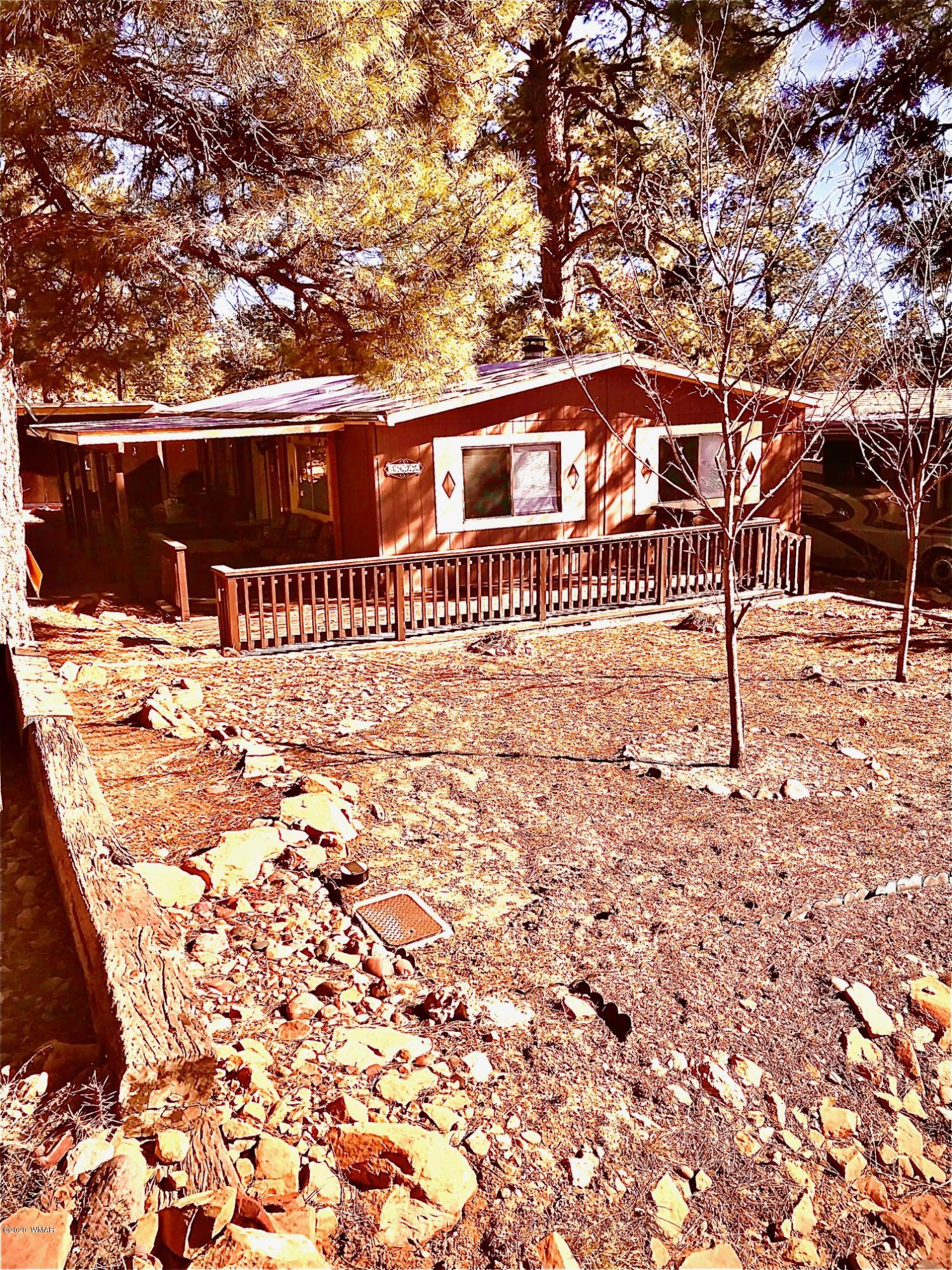 Very efficient, cute and affordable hacienda in the pines.  It has a large covered deck on the front porch and pines on the property. This well cared for property is in a well established neighborhood.  In 2017, it was remodeled to reflect new interior paint, exterior deck, new kitchen cabinets, sink, new bathroom vanities, toilets, ceiling fans and all new flooring. A nice BBQ area and patio porch where family and friends can enjoy the wonderful weather of the White Mountains. Call today for more details. Furnished inside and patio furniture, to convey outside of escrow.