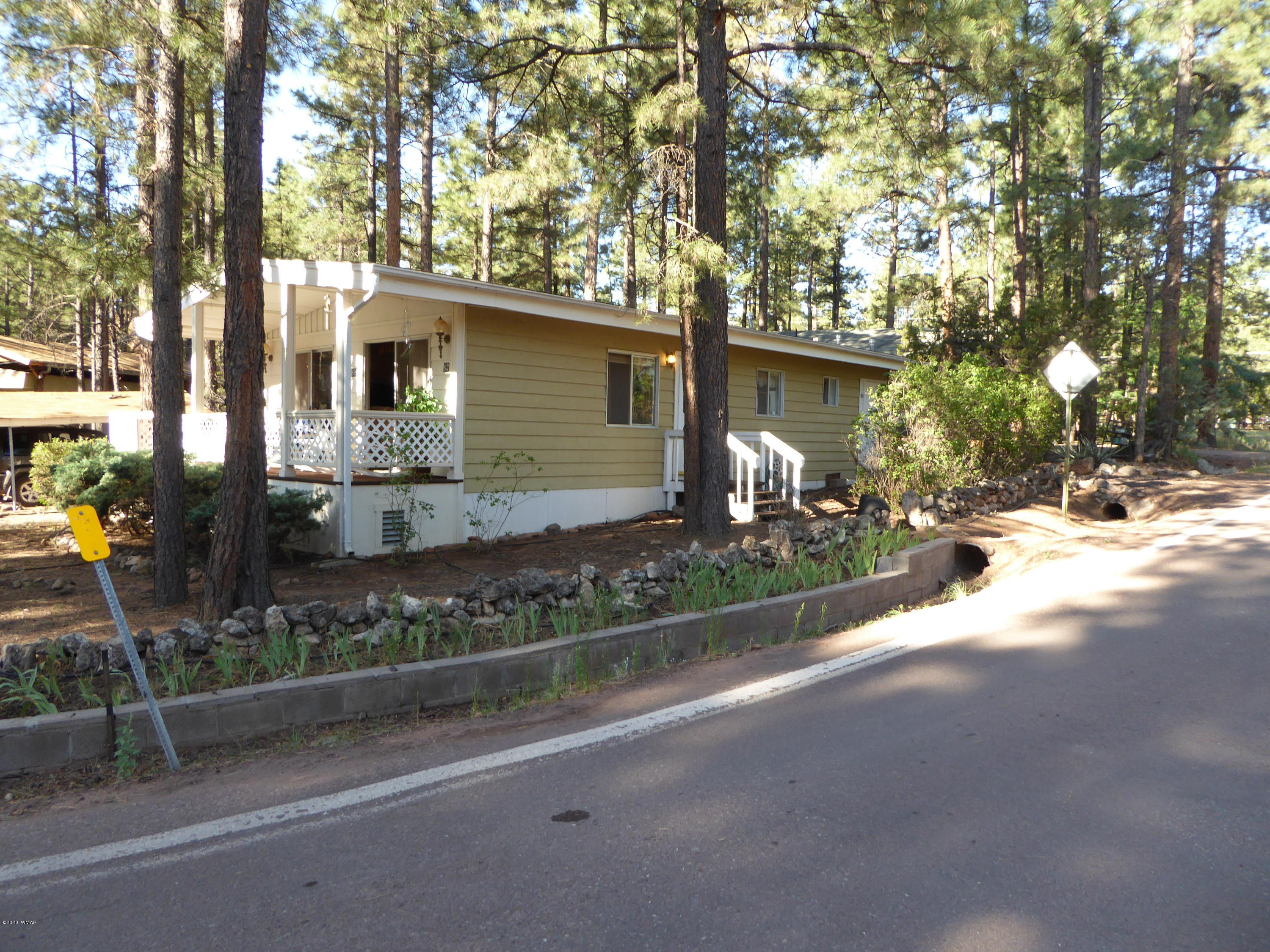 Nice double wide manufactured home nestled on a beautiful treed lot. Enjoy the Ponderosa pines in the front yard from the covered deck. This is a great ''pack & play home,enjoy all the out door spaces. The electric fire place in the living room has only been used one season. This home is move in ready and the furniture stays with the property. It has a chain link fence wrapping around the backyard with storage/workshop at back of property. Home is covered with home warranty which is transferable. The sellers will pay to extend the warranty for one year or buyers choice. not to exceed $500,00