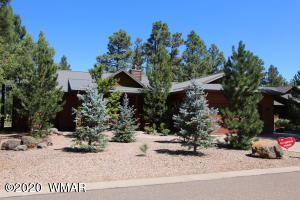 Front of home with blue spruce pine trees