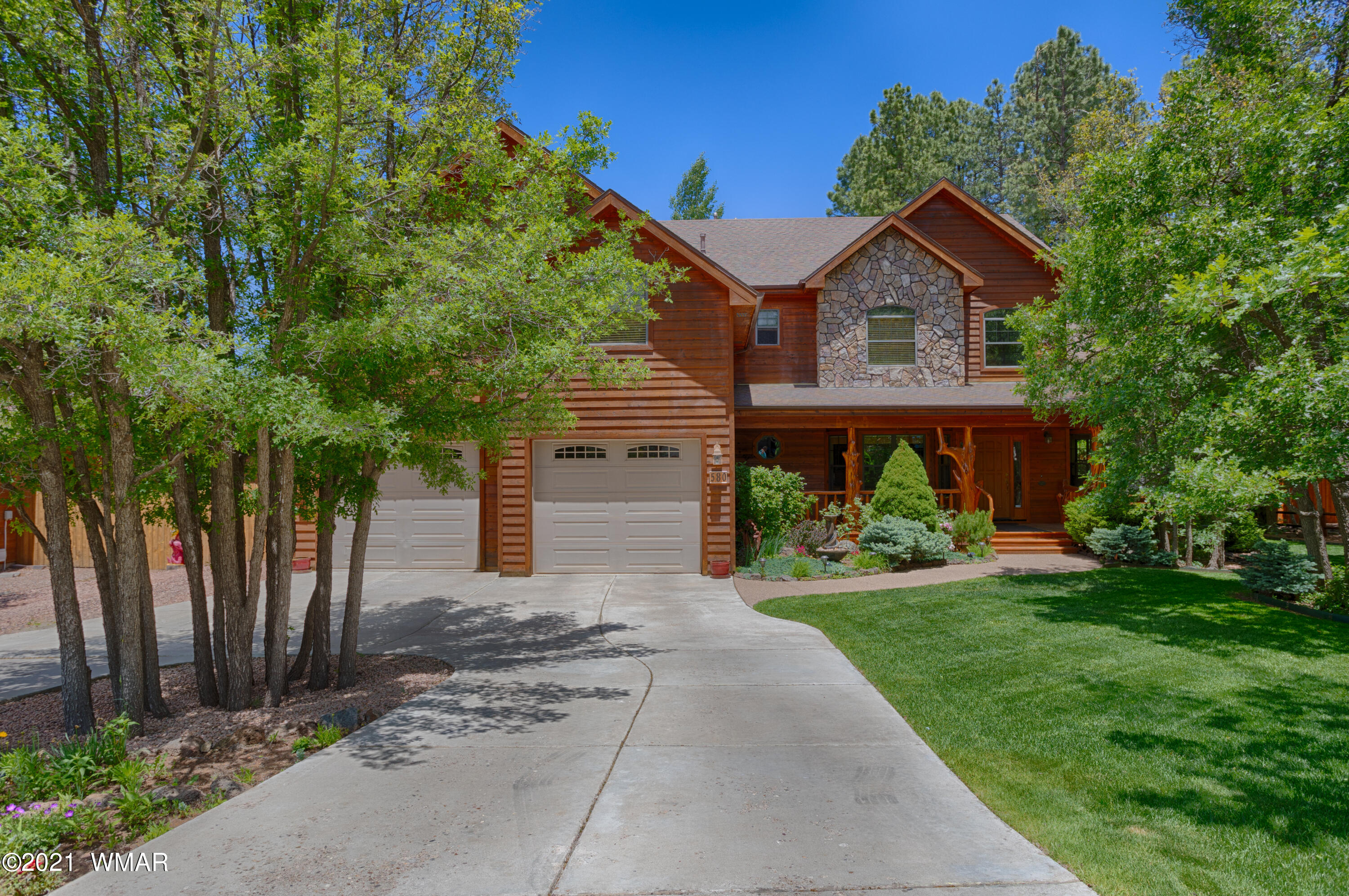 """Gorgeous Woodland Hills home centrally located in Pinetop!  This large 3960 square foot home with 5 bedrooms and 3.5 bathrooms has everything you are looking for.  From the moment you enter onto the property you are greeted by an immaculate front yard with well established trees, shrubs and perennials.  The welcoming front porch and front foyer invites you into the beautiful home with many different wood features like the solid Oak flooring to the Juniper wood railing.  The natural light flows throughout the many downstairs entertaining areas like the living room/dining room with a gas fireplace, the family room with a wood burning stove or the open kitchen/dining room with features like 3 different ovens!  (continued) The upstairs special features include the main master bedroom with its own gas fireplace & master bathroom, three separate guest bedrooms & guest bathroom,  a large entertainment room and ample amounts of storage.  When walking out onto the back porch you will have an """"awe"""" moment as you take in the large porch, beautiful landscaping, ramada and different outdoor living areas. The oversized two car garage is perfect for all with its ample amount of storage areas and ceiling hangers & hooks. Other special features & home layout description is below.  This home will not last long, make an appointment today for a private tour.  Other Special Features: Exterior & back porch staining was just completed Office with built in shelves & drawers Hot water heater is 75 gallons and has a recirculating hot water pump Outdoor shed Furnishings are negotiable on a separate bill of sale outside of escrow. Hook up is in place for an AC unit  Antler chandelier above living room dining table DOES NOT convey Outdoor sauna & grill *may* be negotiable.    Layout: Downstairs features a welcoming entryway, office with built-in shelving and drawers, living room/dining area with gas fireplace, powder room, family room with wood burning stove, downstairs guest master bedroom wit"""