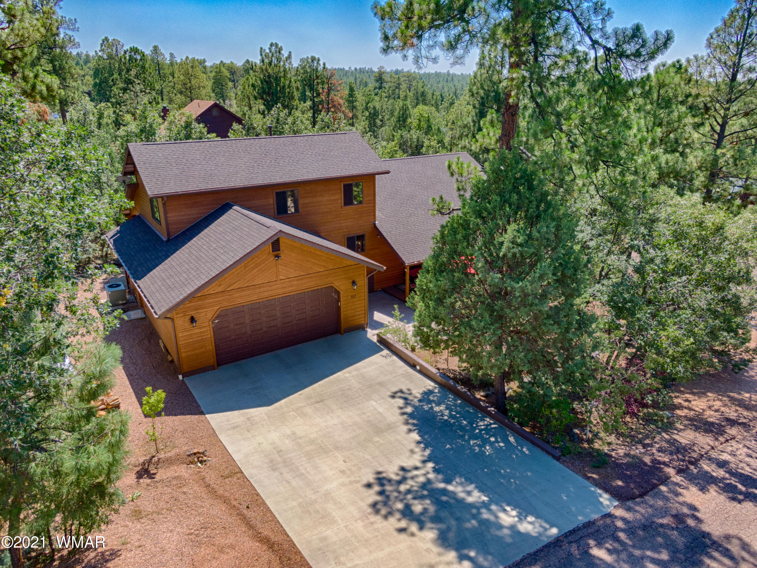 Beautiful cabin on a corner lot at The Woods in Pinetop. Original owners with pride of ownership throughout! Large wrap around deck greets you as you enter this home. A grand entrance with open great room, dining and kitchen. Maple floors, granite countertops, custom cabinets, incredible floor to ceiling stone fireplace, split bedroom floor plan, large windows throughout letting the beautiful mountain sky come through. Garage with epoxy floors, and so much more!  NO HOA.   Home is occupied but easy to show. Use showing time. PLEASE REMOVE SHOES OR USE THE BOOTIES BY THE DOOR WHERE THE LOCKBOX IS HANGING. THANK YOU.
